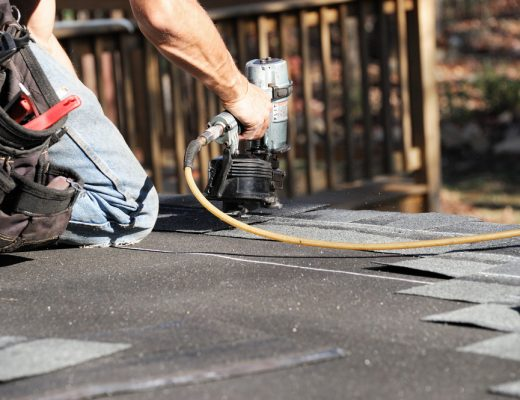 roofer-with-nailgun-installing-roofing-shingles